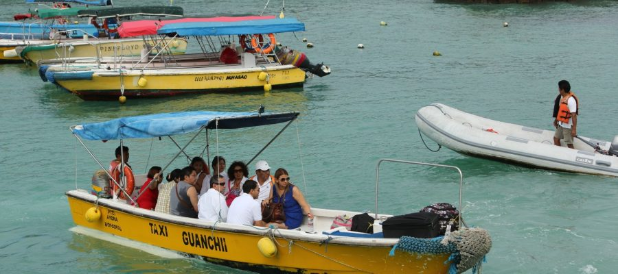 Tourists ride a water taxi in Puerto Ayora, Santa Cruz Island. This is a common mode of transport here.