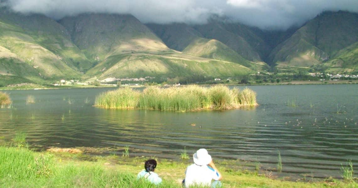 Im Gras am Ufer eines Sees im Hochland die Ruhe genießen . Beste Reisezeit Ecuador und Galapagos-Inseln