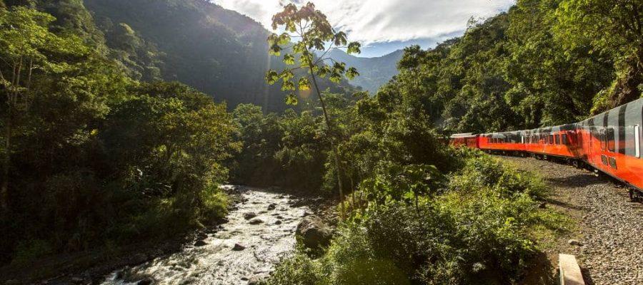 Durch die Berge, am Fluß entlang, schlängelt sich der rote Tren Crucero- Zug durch die Bergwelt - Reisen in Ecuador und Galapagos-Inseln