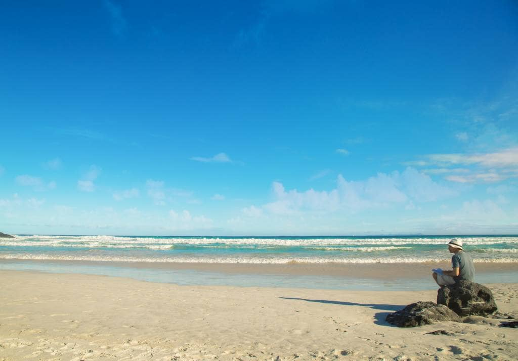 Mit Blick auf das türkisfarbene Meer vom weißen Strand aus - Die beste Reisezeit Ecuador und Galapagos-Inseln