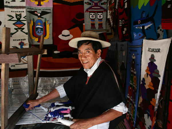 Das Bild zeigt einen freundlichen Handwerker an seinem Arbeitsplatz in der Ecuadorianischen Handwerkerstadt Otavalo