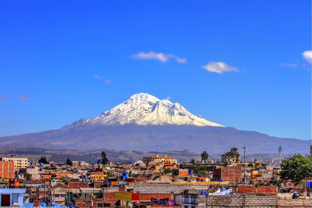 Ein schöner Blick über die Dächer von Riobamba auf den im Sonnenlicht liegenden Chimborazo