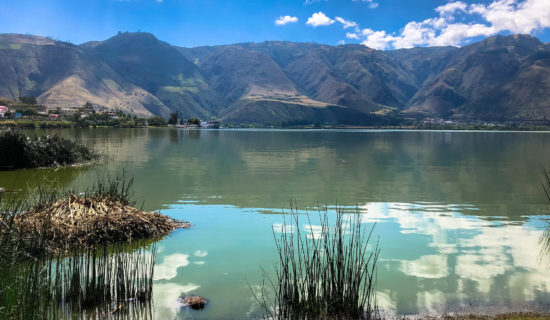 Die Laguna de Yahuarcocha, Ibarra bei Ecuador. Blick über das Wasser auf die Bergkette unter blauem Himmel dahinter, atemberaubend und wunderschön.