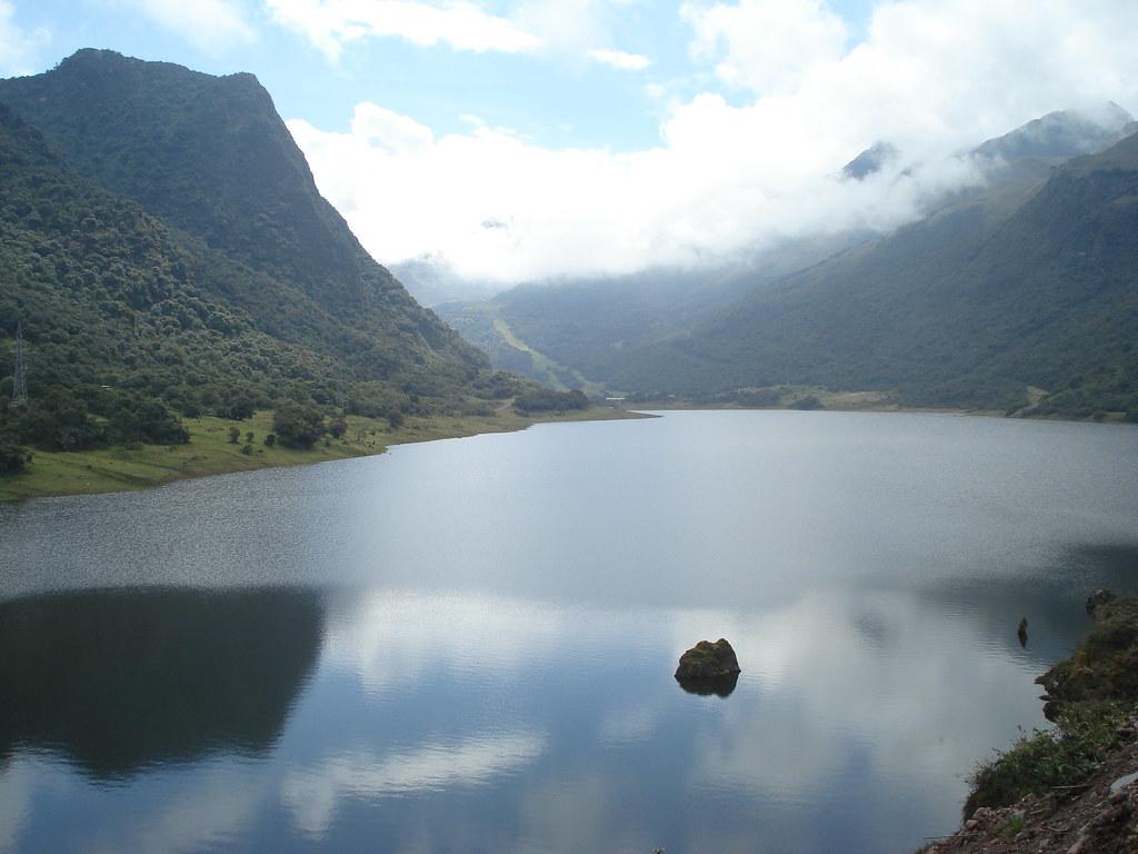 Ein See bei Papallacta in Ecuador, inmitten von im Nebel verschwindenden Bergen.