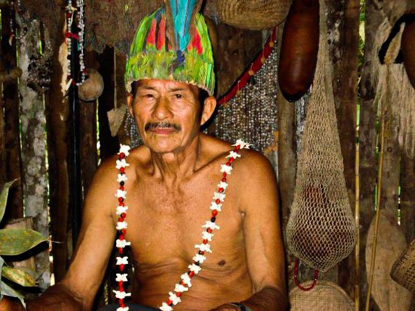 Ein Shamane der Shuar-Gemeinde bei Tena in Ecuador, sitzend in seiner Hütte mit speziellem Farbenfrohen Kopfschmuck.