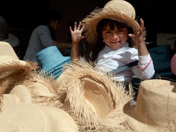 Ein glückliches Kind sitzt mit Hut inmitten von Panamahüten und grinst in die Kamera