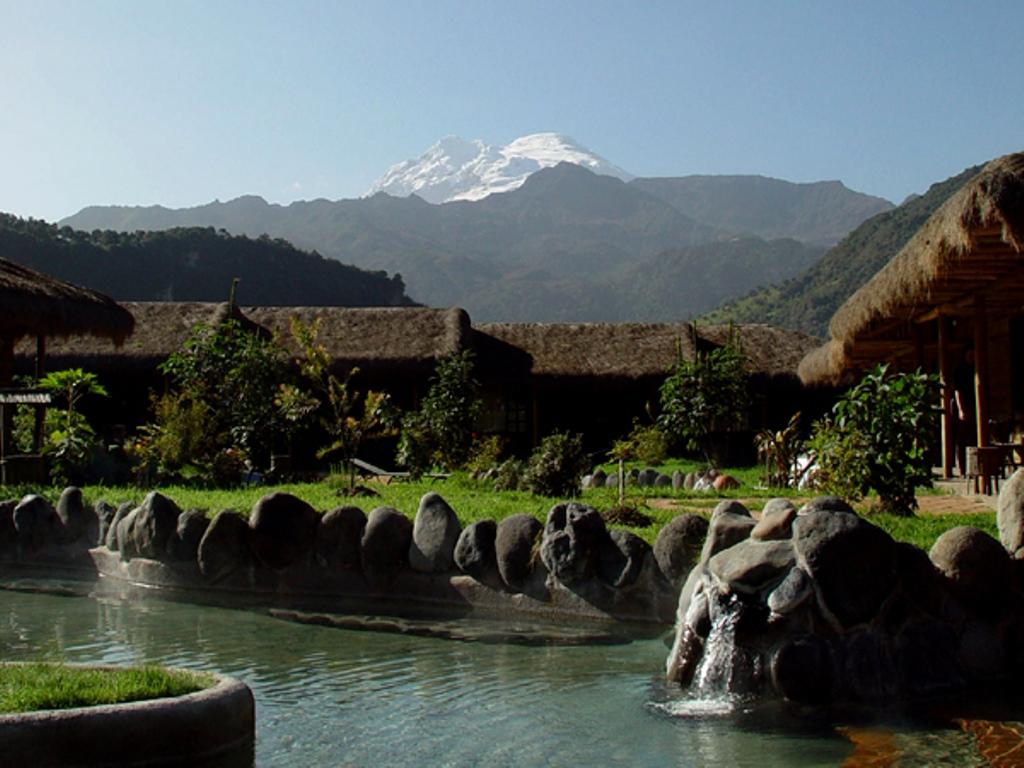 Ein beeindruckender Blick in Ecuador Papallacta Spa. Vom Natursteinbecken sieht man die Landschaft und den verschneiten Vulkangipfel in der Ferne.